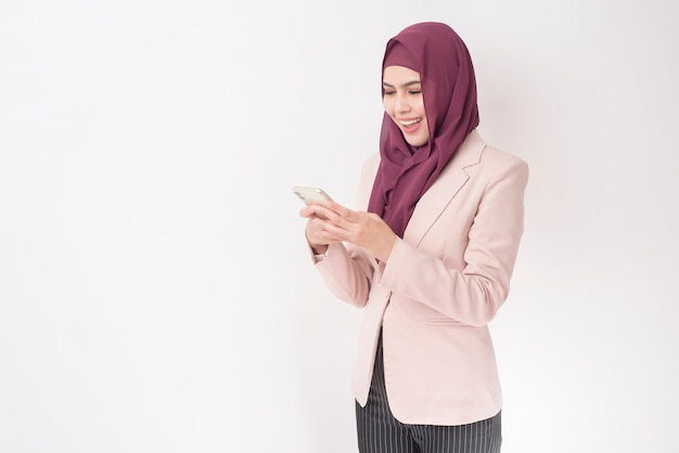 Beautiful business woman with hijab portrait on white wall