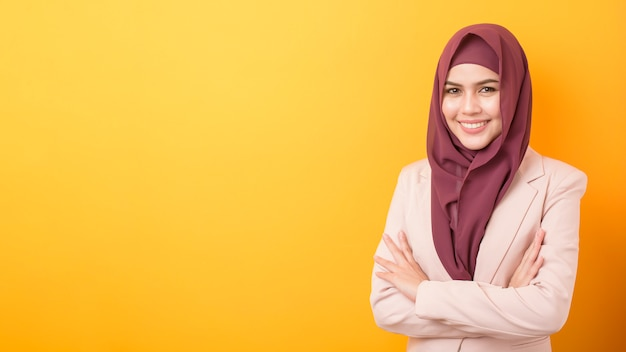 Beautiful business woman with hijab portrait on yellow background
