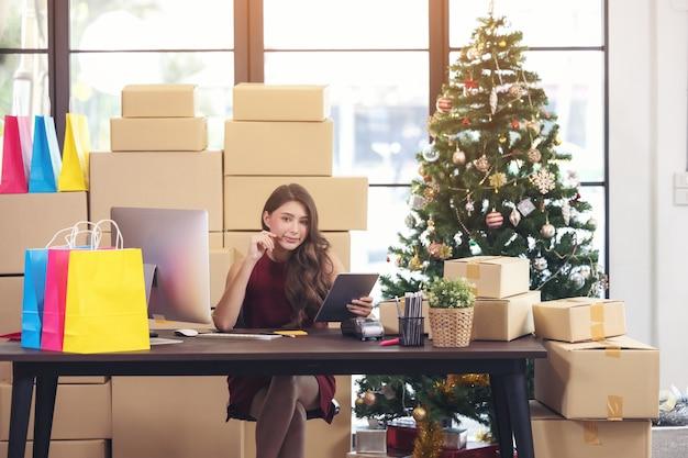 タブレットがオフィスの机に座っている美しいビジネス女性。