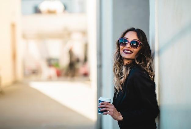 テイクアウトコーヒーとサングラスを持つ美しいビジネス女性。コーヒーブレイクの女の子。