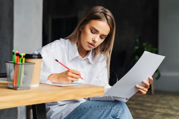 Красивая деловая женщина работает над проектом, сидя за деревянным столом