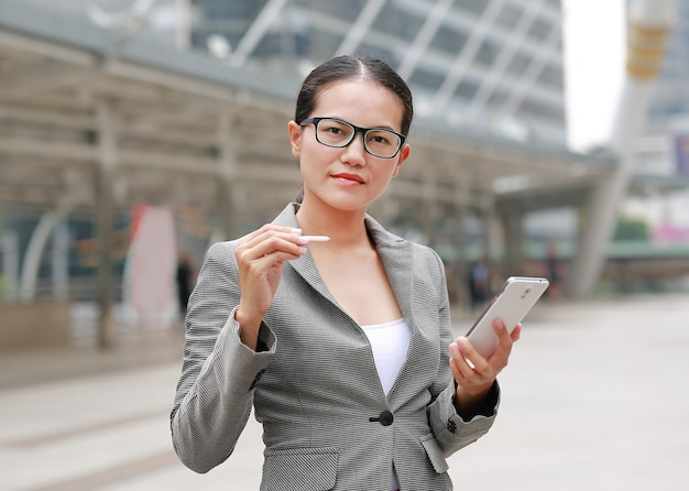 Beautiful business woman working on a smartphone in her hands outdoors.