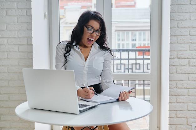 窓の近くの机に座って、コンピューターのラップトップで作業する美しいビジネス女性