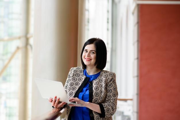 Красивая деловая женщина, работающая с ноутбуком и планшетом
