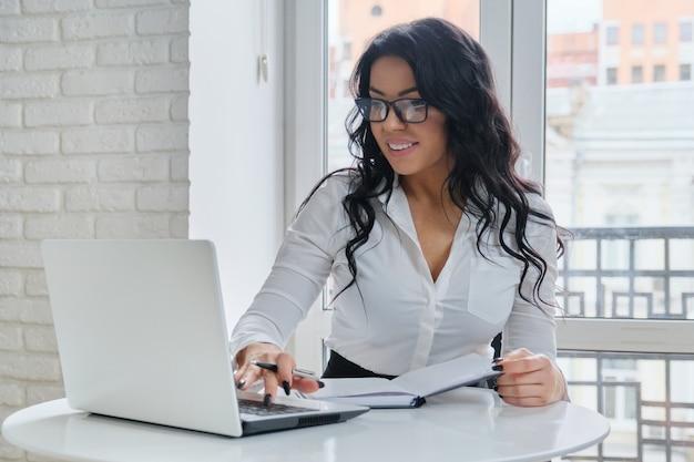 窓の近くの机に座って、ラップトップで作業する美しいビジネス女性。ビジネスノートに書く白いシャツのファッショナブルな女性