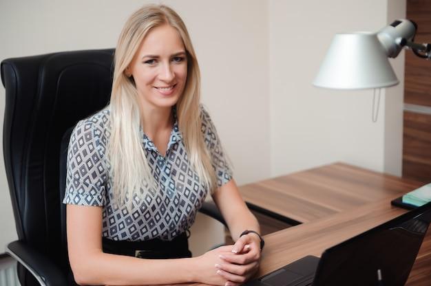 Красивая бизнес-леди работая с продажами в ее офисе.