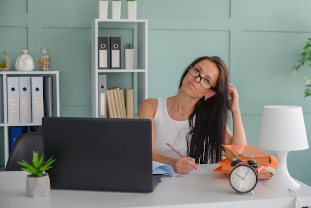 Красивая деловая женщина работает в офисе на ноутбуке фрилансер на работе преподает учитель