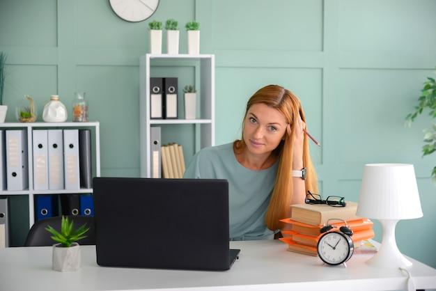 Красивая деловая женщина работает в офисе на ноутбуке фрилансер на работе