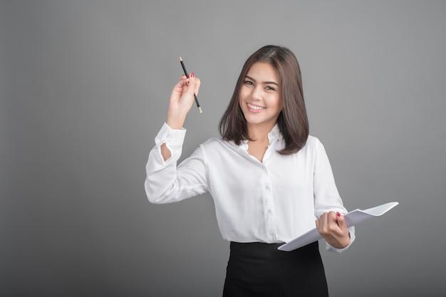 Beautiful business woman writing something on grey background