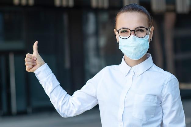 美しいビジネスの女性、屋外に立っているメガネの白いシャツで彼女の顔に医療用防護マスクの少女は、ジェスチャーのように親指を表示します。コロナウイルス、ウイルス、流行、covid-19コンセプト
