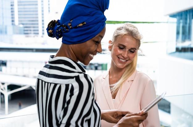 공항에서 일하는 아름다운 여성 사업가들이 여행을 떠나고 있습니다. 스마트폰을 사용하여 전화 걸기