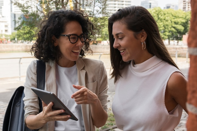 Beautiful business women looking at a tablet outside