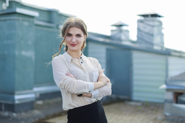 Beautiful businesslady in white blouse, watch and black skirt stand on the roof
