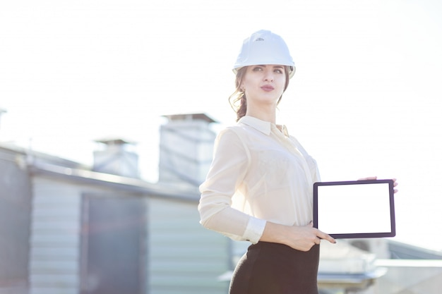 Beautiful businesslady in white blouse, watch, helmet and black skirt stand on the roof and show empty tablet