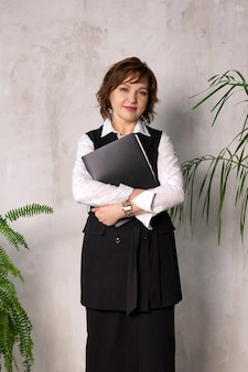 The beautiful, businesslike, successful, mature woman stands with a folder in her hand
