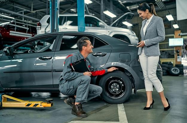 Красивая деловая женщина и механик автосервиса обсуждают работу. ремонт и обслуживание автомобилей.