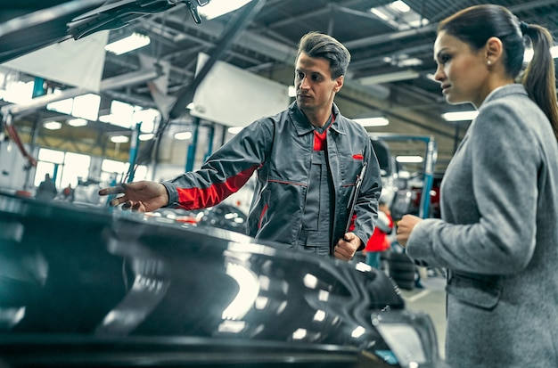 Beautiful businesswoman and auto service mechanic are discussing the work. car repair and maintenance.