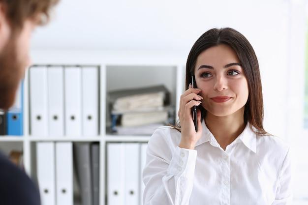 Брюнетка красивая бизнесвумен разговаривает по телефону в офисе