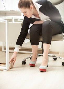 Beautiful businesswoman changing shoes under table at office