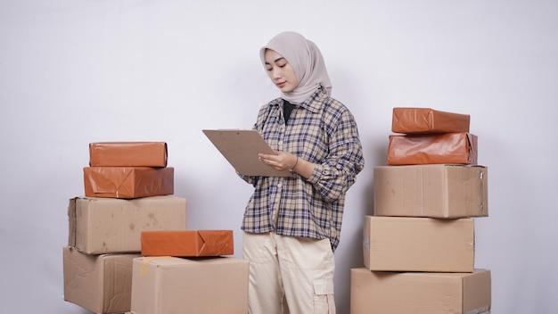 彼らは白い背景で隔離で送信される前にパッケージをチェックする美しい実業家