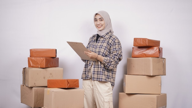 Beautiful businesswoman checking packages before they are sent isolated on white background