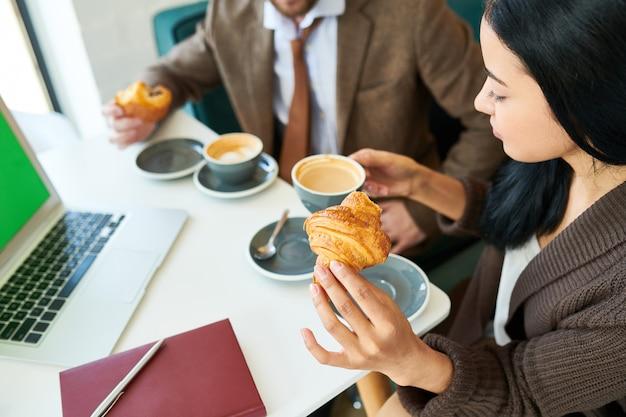 朝食にクロワッサンとコーヒーを楽しむ美しい女性実業家