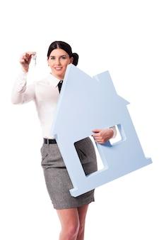 Красивая деловая женщина держит знак дома и ключи для него