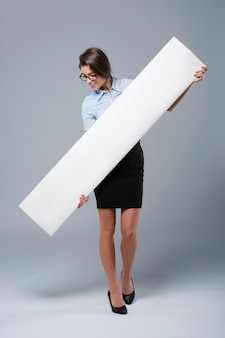 Beautiful businesswoman holding white banner