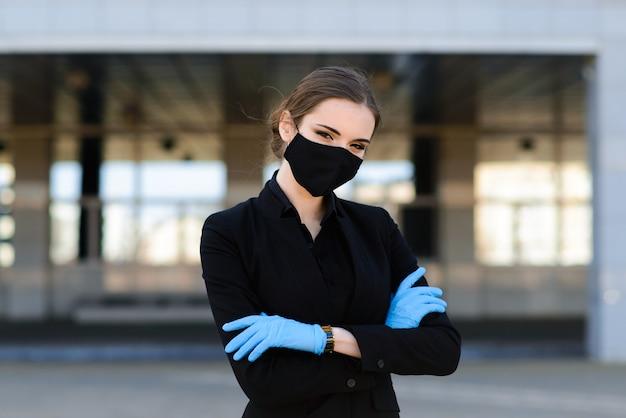 Красивая коммерсантка в черном костюме в черной медицинской маске и перчатках на городе в карантине и изоляции. пандемия covid-19. выборочный фокус