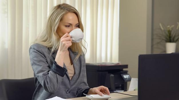 Красивая деловая женщина в костюме работает с чашкой кофе на рабочем месте.