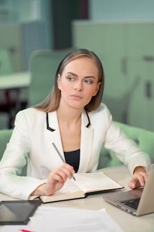 ノートパソコンの前に座ってペンを持って日記にメモをとっている白いジャケットを着た美しい実業家。