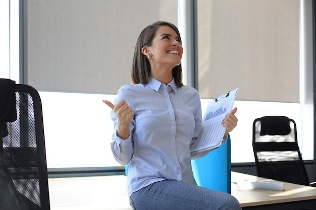 Красивая деловая женщина выражает радость в офисе, получив хорошие новости.