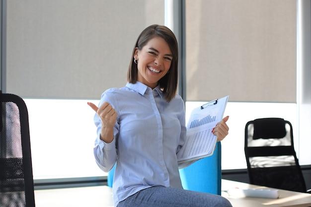 아름다운 여성 사업가가 좋은 소식을 받으면서 사무실에서 즐거운 표정을 짓고 있습니다.