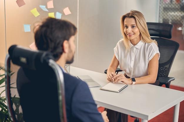 男を見て、ノートとテーブルに座って笑っている美しい実業家