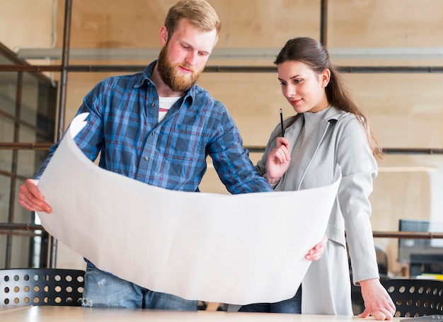 Beautiful businesswoman looking at blue print hold by her male colleague