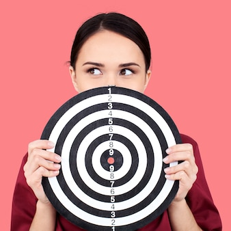 Beautiful businesswoman portrait holding round target of darts, isolated.