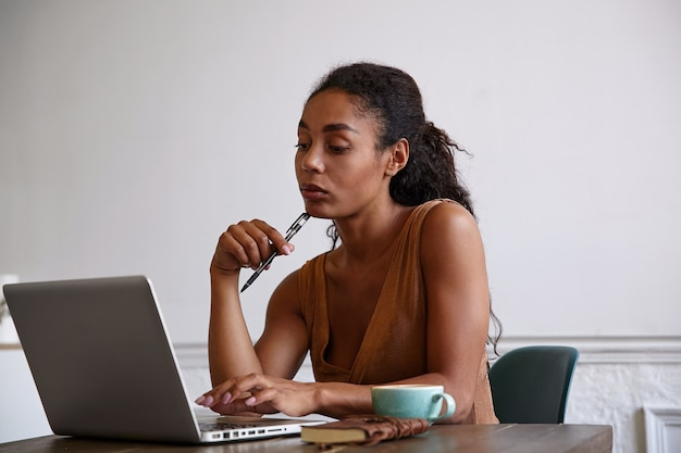 美しい実業家がペンを手に持ってあごに寄りかかってレポートを作成し、コーヒーを飲み、モニターを真剣に見ている