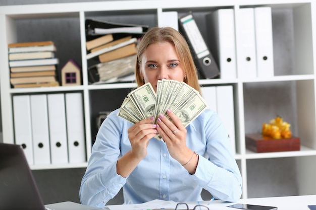 Beautiful businesswoman showing money