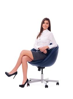 Bella donna di affari che si siede su una sedia