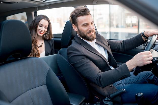 도시에서 차를 운전하는 우아한 남자와 뒷좌석에 앉아 있는 아름다운 사업가