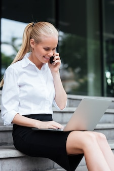 Beautiful businesswoman talking on phone and using laptop while sitting on the stairs outdoors