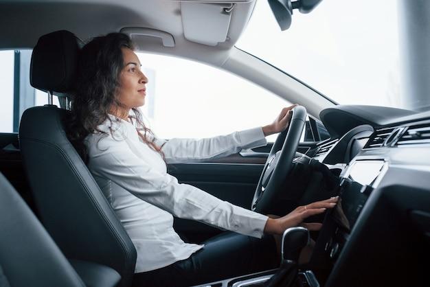Красивая деловая женщина пробует свою новую машину в автомобильном салоне.