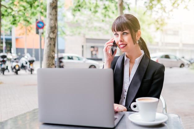 Красивая деловая женщина с помощью ноутбука, сидя в кафе на открытом воздухе и с помощью смартфона