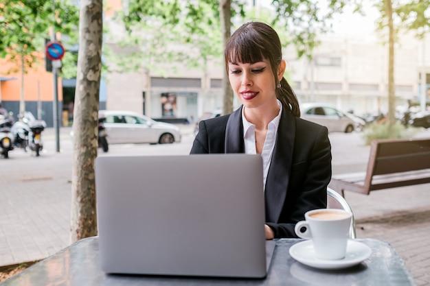 Красивая деловая женщина с помощью ноутбука, сидя в кафе на открытом воздухе