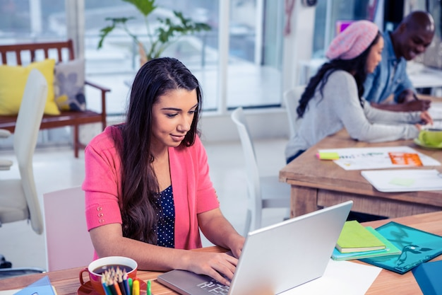 Beautiful businesswoman using laptop while working with colleagues in creative office