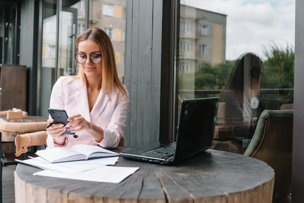 カフェで携帯電話を使用して美しい女性実業家