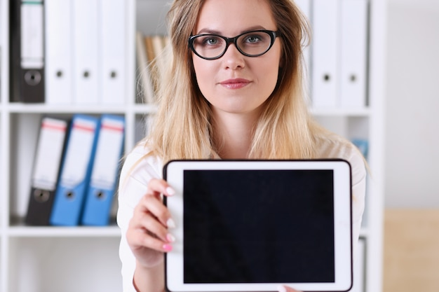Beautiful businesswoman wearing glasses portrait at the office holding a tablet in hand sitting at the table smiling and looking at the camera teacher expresses success checking the test papers.