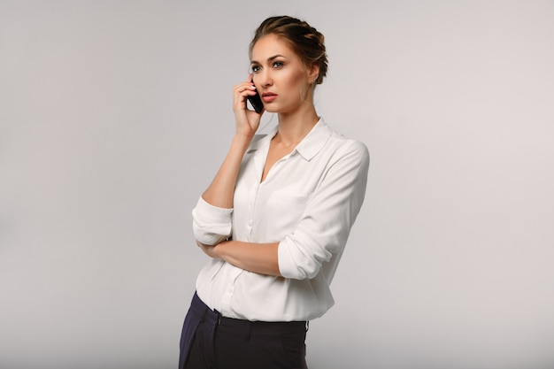 Beautiful businesswoman with a cell phone in hands. serious conversation. business portrait