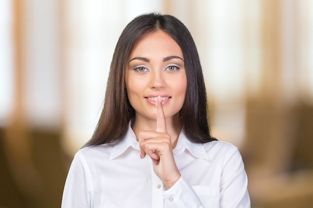 Beautiful businesswoman with finger on lips