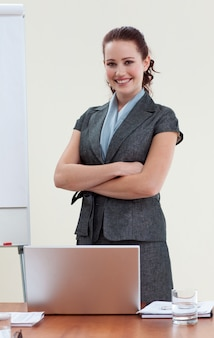 Beautiful businesswoman with folded arms in office